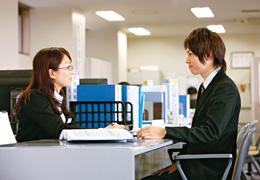 写真:就職課の職員に個別指導を受けているスーツ姿の男子学生